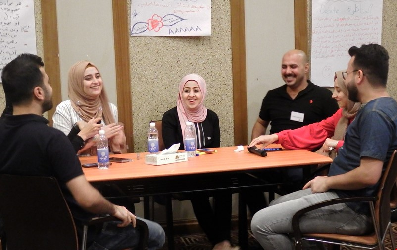 Young Iraqi peacebuilders sitting around a table.