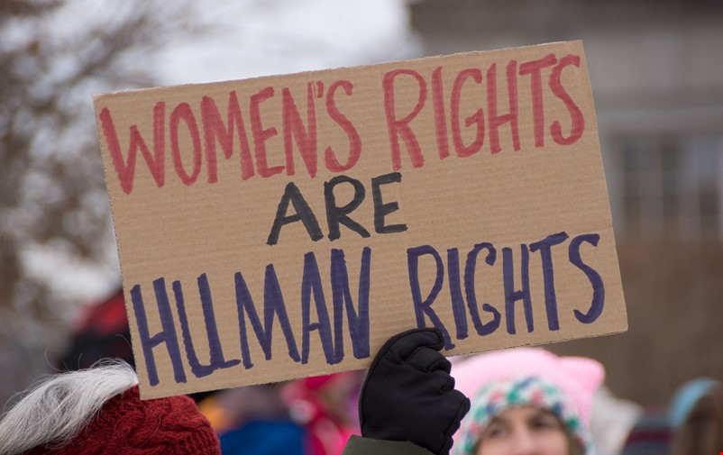 Hand holding a sign that says: Womens rights are human rights.