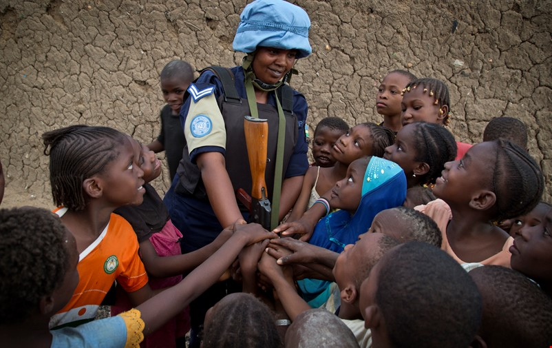 Female UN-soldier surrounded by children in Mali.