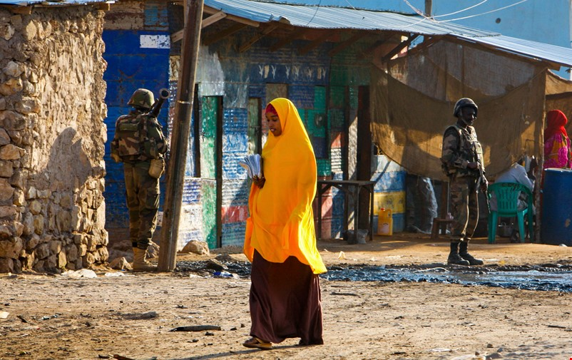 A woman walking past military men in Somalia.